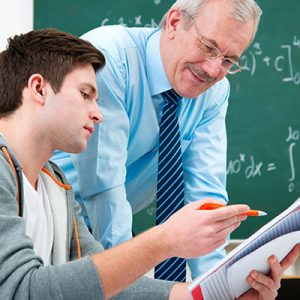 FE jobs allow you to help students reach their potential as seen in this image of a higher ed teacher and student